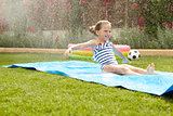 Girl Having Fun On Water Slide In Garden