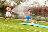 Father Spraying Son With Garden Hose
