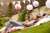 Father With Daughter Relaxing On Rug In Garden Together