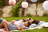 Family With Baby Relaxing On Rug In Garden Together