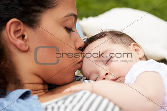 Close Up Of Mother With Baby Relaxing On Rug In Garden