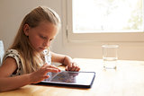 Young Girl At Home Using Digital Tablet On Kitchen Table