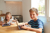 Children At Home Using Digital Devices On Kitchen Table