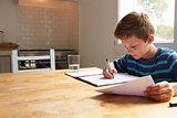 Boy Doing Homework Sitting At Kitchen Table