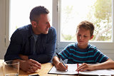 Father Helping Son With Homework Sitting At Kitchen Table