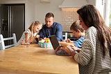 Family Using Digital Devices At Kitchen Table