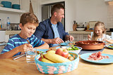 Father And Children At Home In Eating Meal Together