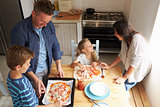 Family At Home In Kitchen Making Pizzas Together