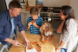 Family At Home In Kitchen Eating Homemade Pizza Together