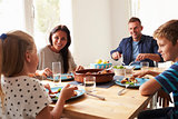 Family At Home In Eating Meal Together