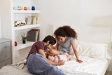 Parents Playing With Baby Daughter In Bedroom At Home