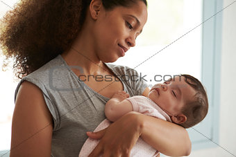 Close Up Of Mother Cuddling Sleeping Baby Daughter At Home