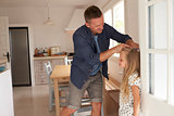 Father Measuring Daughter's Height Against Wall