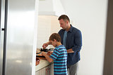 Father And Son In Kitchen Making Pizzas Together