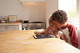 Children At Home Using Digital Tablet On Kitchen Table