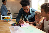 Children And Father Painting Picture On Kitchen Table