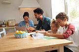 Children Paint At Kitchen Table As Parents Look At Laptop