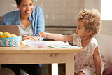 Girl Paints At Kitchen Table As Mother Works At Laptop