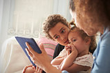 Mother And Children Sitting On Sofa Using Digital Tablet