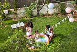 Overhead View Of Family Having Fun In Garden Paddling Pool