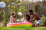 Family Having Fun In Garden Paddling Pool