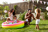 Family Having Fun In Garden Paddling Pool