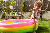 Girl Having Fun In Garden Paddling Pool
