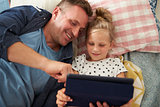 Father And Daughter Lying On Floor Using Digital Tablet