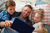Father And Children Lying On Floor Using Digital Tablet