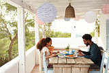 Couple Enjoying Outdoor Meal On Terrace Together