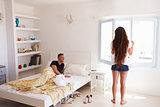 Woman opening window in sunlit room, her partner lies in bed