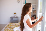 Woman opening bedroom window, her partner in bed, side view