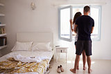 Couple by window in sunlit bedroom, back view full length