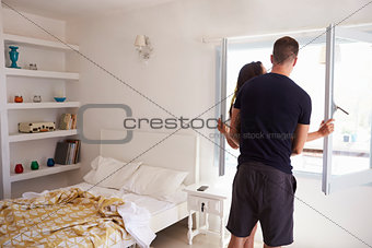 Couple by window in bedroom, back view three quarter length