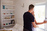Couple embrace by window in bedroom, back view waist up