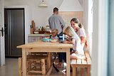 Kids do homework at kitchen table with mum while dad cooks