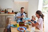 Family sitting around kitchen table serving lunch