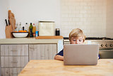Young boy using laptop computer at kitchen table