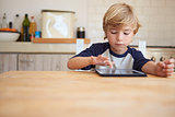 Young boy using tablet computer at kitchen table, front view