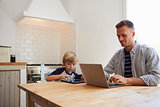 Father and son using computers at the kitchen table