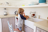 Young boy kneeling on a chair to wash dishes, full length