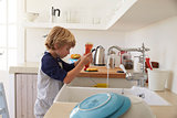 Boy squeezing washing up liquid into sink to wash dishes