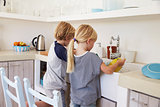 Brother and sister kneeling at sink to wash up in kitchen
