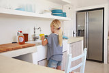 Young girl kneeling on chair washing up, back view