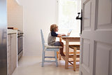Young boy using laptop in kitchen, side view, from doorway