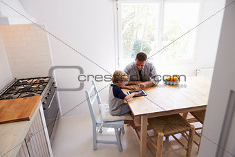 Dad and son use tablet in kitchen, elevated view from doorway