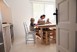 Mum and two kids working at kitchen table, seen from doorway