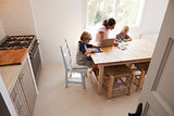 Mum and two kids working at kitchen table, elevated view
