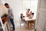 Dad cooking and mum with kids at the kitchen table
