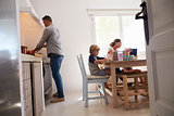 Dad cooking and mum with kids at kitchen table, low angle